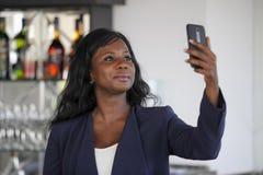 拍selfie与手机的偶然典雅的衣裳的愉快的黑人美国黑人的妇女画象照片 免版税库存图片