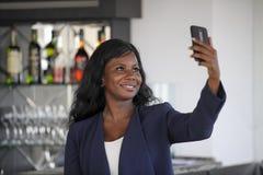 拍selfie与手机的偶然典雅的衣裳的愉快的黑人美国黑人的妇女画象照片 免版税库存照片