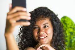 拍selfie与手机的年轻可爱和美丽的愉快的黑人美国黑人的妇女画象照片在假日apartm 库存图片