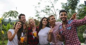 拍Selfie照片使用细胞巧妙的电话烹调烤肉朋友小组的青年人聚集在夏天大阳台谈话 股票视频