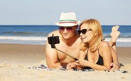 拍selfie照片用在海滩的selfie棍子的愉快的夫妇 免版税库存图片