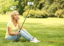 拍selfie照片用棍子的少妇在公园 库存照片
