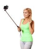 拍selfie照片用棍子的少妇被隔绝 免版税库存照片