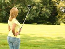 拍selfie照片用棍子的白肤金发的少妇在公园 免版税库存图片