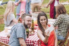 拍selfie照片的一对年轻夫妇在周末BBQ集会出口 图库摄影
