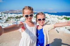 拍selfie照片的两个女孩户外有在希腊村庄和海的惊人的看法 免版税库存图片