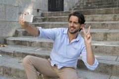 拍selfie照片的城市楼梯的年轻可爱的拉丁人获得在手机的乐趣 免版税库存照片