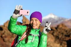 拍selfie照片的妇女远足者远足在冬天 免版税图库摄影