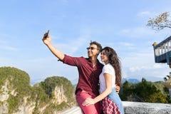 拍Selfie照片的年轻夫妇山景城点愉快的微笑的男人和妇女细胞聪明的电话亚洲人假日 库存照片