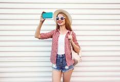 拍selfie照片的愉快的微笑的妇女由在夏天回合草帽,方格的衬衣,在白色墙壁上的短裤的电话 免版税库存照片