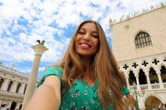 拍selfie照片的愉快的美丽的妇女在有白色云彩的威尼斯在天空 微笑对照相机的旅游女孩 免版税库存照片