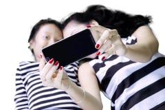 拍selfie照片的母亲和女儿 免版税库存图片