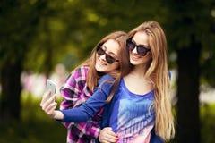 拍selfie照片的美丽的朋友 免版税库存图片