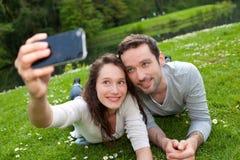 拍selfie照片的年轻夫妇在公园 免版税库存图片