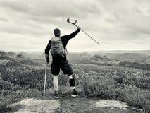 拐杖的残疾人在岩石 在氯丁胶金属护膝垫的疼的膝盖和人拿着前臂拐杖 免版税图库摄影