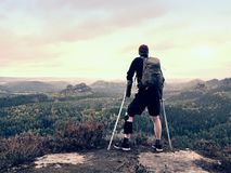 拐杖的残疾人在岩石 在氯丁胶金属护膝垫的疼的膝盖和人拿着前臂拐杖 免版税库存照片