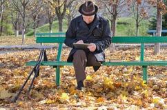 拐杖的年长人使用一种片剂在公园 免版税库存照片