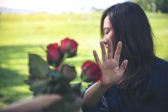 拒绝一朵红色玫瑰的亚裔妇女从她的男朋友开花在华伦泰` s天 免版税库存照片