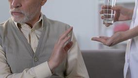 拒绝年长的人从医护人员,不需要的治疗,健康的药片 股票录像