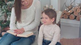 拒绝的小男孩与他的妈妈一起读书在圣诞前夕 免版税库存图片