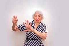拒绝提议用她的手的被触犯的老资深妇女 库存图片