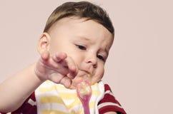 拒绝逗人喜爱的婴孩吃从匙子的婴儿食品 图库摄影