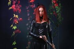 拔出在秋天藤中的蓝眼睛的红色顶头哥特式女孩一把幻想剑 免版税库存图片