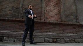 拔出他的从他的口袋的分散的商人手机,他沿沿着a的都市边路走 股票录像
