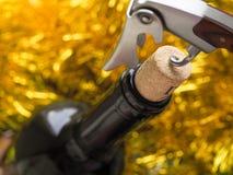 拔塞螺旋打开一个瓶在欢乐明亮的背景的酒 免版税图库摄影