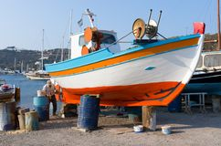 拔摩岛海岛,希腊- 2017年8月22日-一个老人在拔摩岛港口修理他的渔船 免版税库存照片