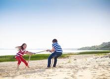 拔河-使用在海滩的男孩和女孩 库存照片