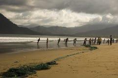 拖拉净额的渔夫 免版税库存照片