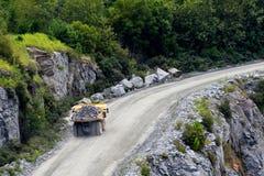 拖拉岩石的翻斗车在采矿和建造场所 免版税库存照片