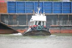 拖拉巨大的河驳船的猛拉小船 免版税库存图片