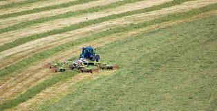 拖拉机切口与干草鲍伯的草地 免版税图库摄影