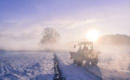 拖拉机剪影通过雾,在多雪的领域 免版税库存图片