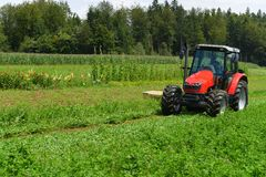 拖拉机割的三叶草领域的有机农夫与转台式切削刀 免版税库存照片