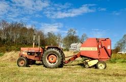 拖拉机和圆的干草打包机 库存照片