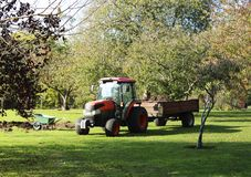 拖拉机和手推车工作的在庭院里 庭院运输 免版税库存图片