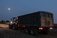 拖拉机和拖车有车灯的在夜间 库存照片