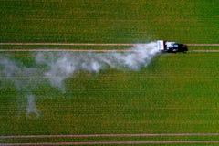 拖拉机喷洒的杀虫剂的空中图象在绿色燕麦领域射击的从寄生虫 免版税库存照片