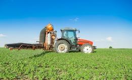 拖拉机喷洒的大豆的农夫 库存图片
