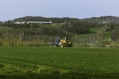 拖拉机喷洒的领域 图库摄影
