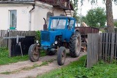 拖拉机在农村房子的围场 免版税库存图片