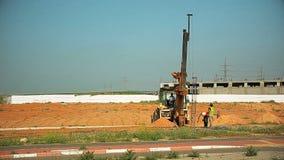 拖拉机在地面的一个孔举钢标尺并且投入了它 建筑工人帮助他 股票视频