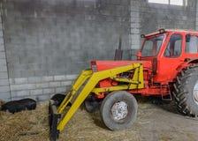 拖拉机在有干草堆的一个棚子 免版税库存图片