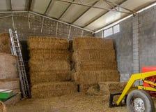 拖拉机在有干草堆的一个棚子 图库摄影