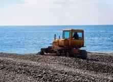 拖拉机在游泳季节前的成水平的石渣海滩 库存照片