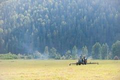 拖拉机在种秣草地 库存图片