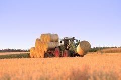 拖拉机在运输干草堆的领域的工作 库存照片